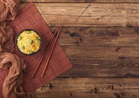 Black bowl with boiled organic basmati vegetable rice with wooden chopsticks on brown placemat with linen towel. Yellow corn and green peas with paprika slices.  Zdjęcie Seryjne