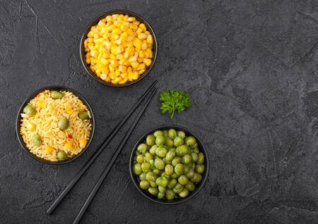 Black bowls with boiled organic basmati vegetable rice, yellow corn and peas with black chopsticks on black stone background. Zdjęcie Seryjne