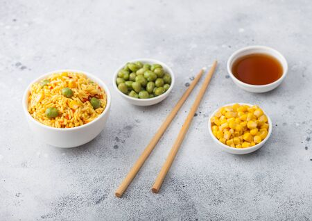 White bowl with boiled organic basmati vegetable rice with wooden chopsticks on light background. Yellow corn and green peas with paprika slices. Zdjęcie Seryjne