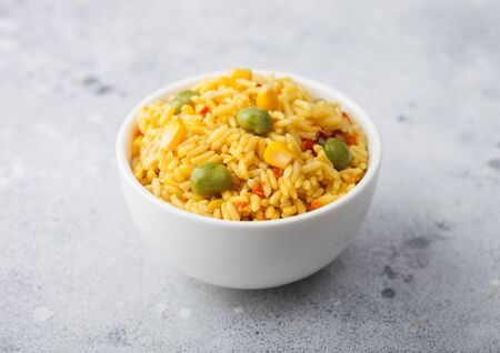 White bowl with boiled organic basmati vegetable rice on light background. Yellow corn and green peas with paprika slices. Zdjęcie Seryjne