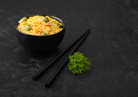 Whi Black bowl with boiled organic basmati vegetable rice with black chopsticks on black background. Yellow corn and green peas with paprika slices.