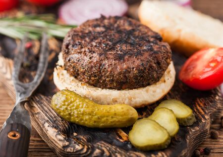 Fresh grilled minced pepper beef burger on vintage chopping board with buns onion and tomatoes on wood background. Salty pickles and fork