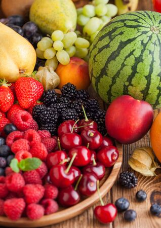 Fresh organic summer berries mix in wooden tray and exotic fruits on wooden background. Raspberries, strawberries, blueberries, blackberries and cherries. Watermelon, pear, pineapple, grapes. Top view