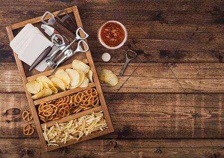 Glass of craft lager beer and opener with box of snacks on wood background. Pretzel and crisps and salty potato sticks in vintage wooden box with openers and beer mats. Stockfoto