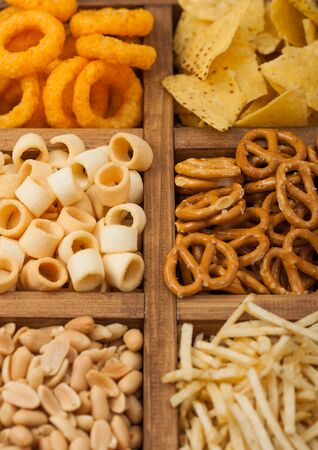 Various snacks in vintage wooden box. Onion rings,nachos, salty peanuts with potato sticks and pretzels. Suitable for beer and fizzy drinks.