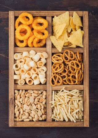 Various snacks in vintage wooden box on wooden background. Onion rings,nachos, salty peanuts with potato sticks and pretzels. Suitable for beer and fizzy drinks.