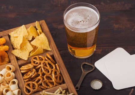 Glass of craft lager beer and opener with box of snacks on wood background. Pretzel,salty potato sticks, peanuts, onion rings with nachos in vintage box with openers and beer mats. Фото со стока