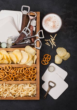 Glass of craft lager beer and opener with box of snacks on black kitchen table background. Pretzel and crisps and salty potato sticks in vintage wooden box with openers and beer mats. Stock fotó