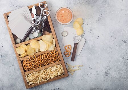 Glass of craft lager beer and opener with box of snacks on light kitchen table background. Pretzel and crisps and salty potato sticks in vintage wooden box with openers and beer mats. Stockfoto