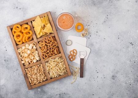 Glass of craft lager beer and opener with box of snacks on light kitchen background. Pretzel,salty potato sticks, peanuts, onion rings with nachos in vintage box with openers and beer mats. Фото со стока