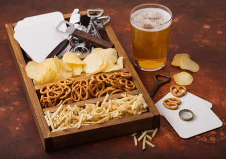 Glass of craft lager beer and opener with box of snacks on brown kitchen table background. Pretzel and crisps and salty potato sticks in vintage wooden box with openers and beer mats.