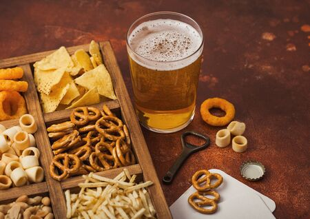 Glass of craft lager beer and opener with box of snacks on brown kitchen background. Pretzel,salty potato sticks, peanuts, onion rings with nachos in vintage box with openers and beer mats.