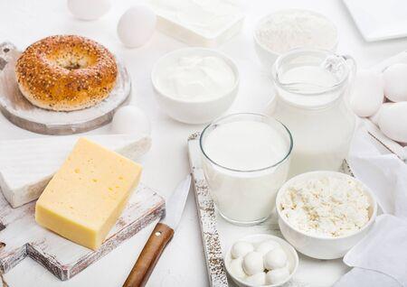 Prodotti lattiero-caseari freschi in scatola di legno d'epoca su sfondo bianco. Barattolo e bicchiere di latte, ciotola di panna acida, formaggio e uova. Bagel al forno fresco sul tagliere rotondo con coltello.