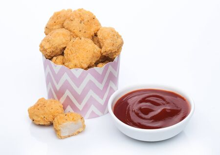 Crunchy chicken popcorn bites in kids paper cup for fast food meals on white with ketchup. Stockfoto