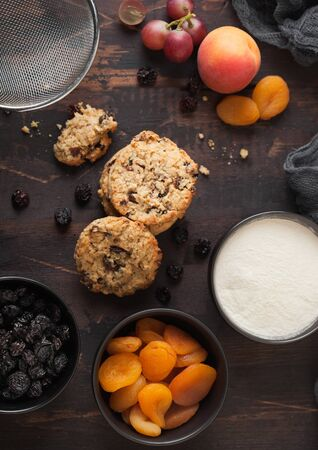 Homemade organic oatmeal cookies with raisins and apricots on wooden background. Black bowl of raisins and dried apricots with flour and fresh fruits.