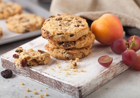 Homemade organic oatmeal cookies with raisins and apricots with baking tray on light kitchen background. Archivio Fotografico - 129486380