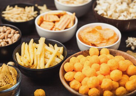 All classic potato snacks with peanuts, popcorn and onion rings and salted pretzels in bowl plates on wood. Twirls with sticks and potato chips and crisps with nachos and cheese balls. Фото со стока
