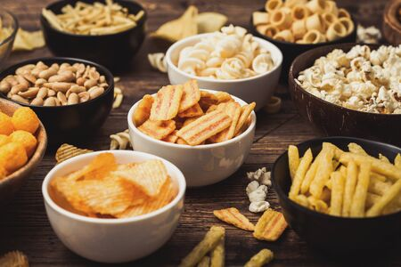 All classic potato snacks with peanuts, popcorn and onion rings and salted pretzels in bowl plates on wood. Twirls with sticks and potato chips and crisps with nachos and cheese balls. Top view Фото со стока
