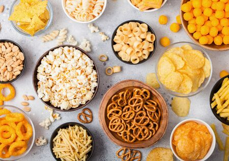 All classic potato snacks with peanuts, popcorn and onion rings and salted pretzels in bowl plates on light table. Twirls with sticks and potato chips and crisps with nachos and cheese balls.