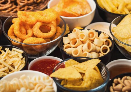 All classic potato snacks with peanuts, popcorn and onion rings and salted pretzels in bowl plates on black table. Twirls with sticks and potato chips and crisps with nachos and cheese balls. Фото со стока