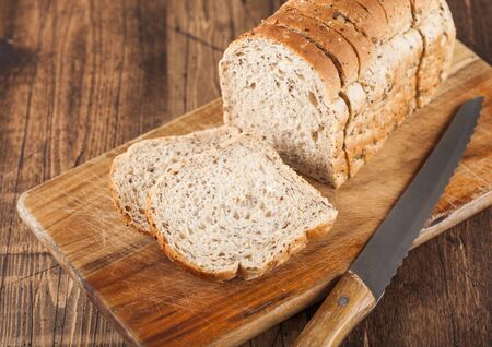 Cut of fresh loaf of seeded bread on wooden background with chopping board and bread knife. Traditional bakery heritage.