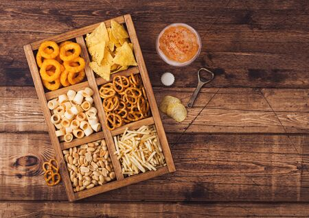 Glass of craft lager beer and opener with box of snacks on wood background. Pretzel,salty potato sticks, peanuts, onion rings with nachos in vintage box with openers and beer mats. Top view