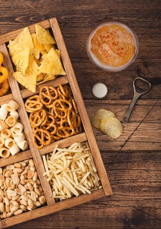 Glass of craft lager beer and opener with box of snacks on wood background. Pretzel,salty potato sticks, peanuts, onion rings with nachos in vintage box with openers and beer mats. Stockfoto