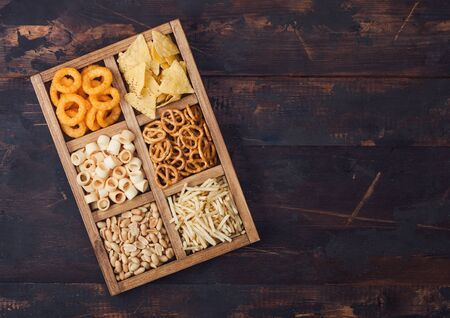 Various snacks in vintage wooden box on wooden background. Onion rings,nachos, salty peanuts with potato sticks and pretzels. Suitable for beer and fizzy drinks. Space for text