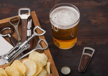 Glass of craft lager beer and opener with box of snacks on dark wood background. Pretzel and crisps and salty potato sticks in vintage wooden box with openers and beer mats.