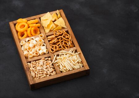 Various snacks in vintage wooden box on black kitchen background. Onion rings,nachos, salty peanuts with potato sticks and pretzels. Suitable for beer and fizzy drinks. Space for text
