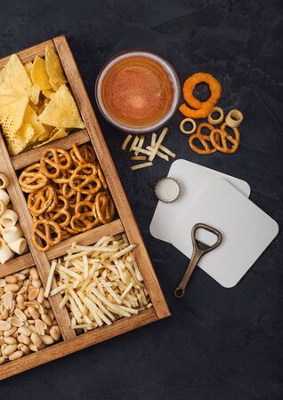Glass of craft lager beer and opener with box of snacks on dark background. Pretzel,salty potato sticks, peanuts, onion rings with nachos in vintage box with openers and beer mats. Top view Stockfoto