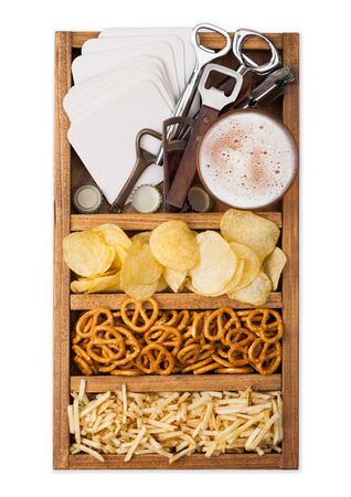 Glass of craft lager beer in vintage box of snacks openers and beer mats isolated on white. Pretzel and crisps and salty potato.
