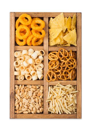 Various snacks in vintage wooden box isolated on white. Onion rings,nachos, salty peanuts with potato sticks and pretzels. Suitable for beer and fizzy drinks.