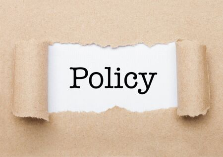 Policy concept text appearing behind torn brown paper envelope