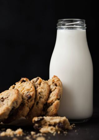 Homemade organic oatmeal cookies with raisins and apricots and bottle of milk on dark wood background.