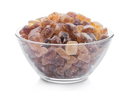 Glass bowl of natural brown caramelized sugar cubes on white.