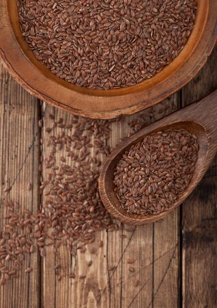 Raw natural organic linseed flax-seed in wooden spoon on wood background. Healthy omega 3 product.