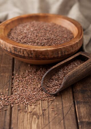 Raw natural organic linseed flax-seed in wooden bowl with spoon on wood background. Healthy omega 3 product.