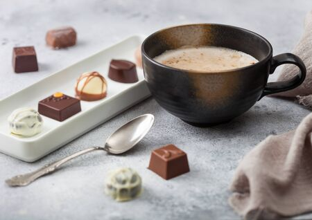 Luxury Chocolate candies in white porcelain plate with cup of cappuccino coffee and silver spoon on light background.