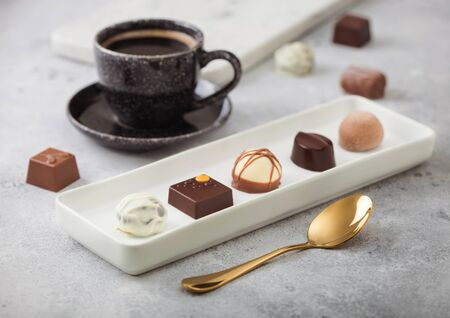Luxury Chocolate candies in white porcelain plate with cup of black coffee and golden spoon on light background. Фото со стока