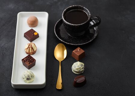 Luxury Chocolate candies in white porcelain plate with cup of black coffee and golden spoon on dark background. Top view