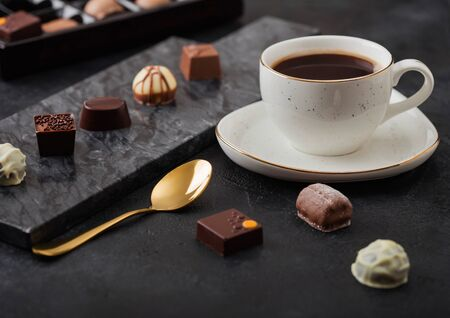 Luxury Chocolate candies selection with cup of black coffee and golden spoon on black marble board and dark background.