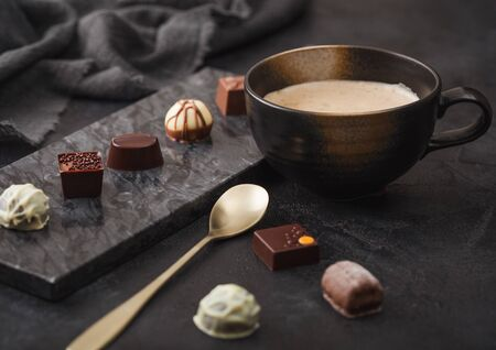 Luxury Chocolate candies selection with cup of cappuccino coffee and dessert spoon on black marble board and dark background. Фото со стока