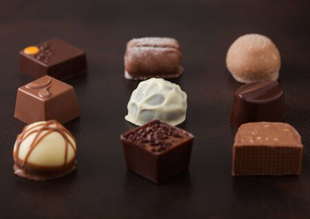 Luxury Chocolate candies selection on brown background.White, dark and milk chocolate assortment.