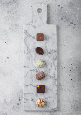 Luxury Chocolate candies selection on light marbel board. White, dark and milk chocolate assortment. Top view
