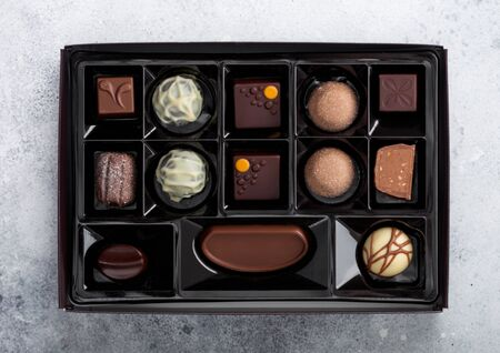 Box of Luxury Chocolate candies selection on light background. White, dark and milk chocolate assortment.Top view