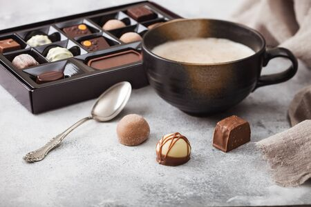 Box of Luxury Chocolate candies selection with cup of cappuccino coffee and silver spoon on light background. Фото со стока