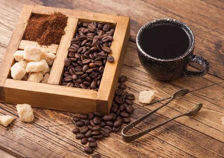 Black ceramic cup of fresh raw organic coffee with beans and ground powder with cane sugar in vintage box on wooden background.