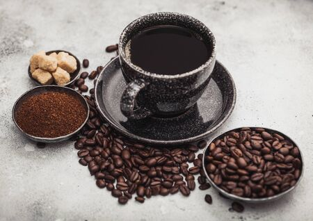 Cup of fresh raw organic coffee with beans and ground powder with cane sugar cubes with coffee tree leaf on light background. Фото со стока