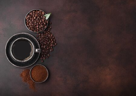 Cup of fresh raw organic coffee with beans and ground powder with cane sugar cubes with coffee tree leaf on dark background. Фото со стока